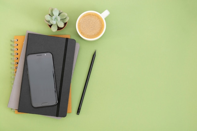Top view of working table. black closed notebook, coffee cup and smartphone. copy space for text. design mock up.