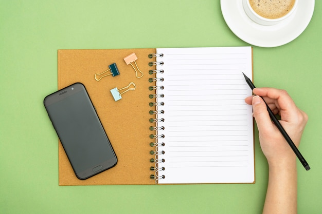 Top view of working table. open notebook, coffee cup, smartphone and a woman hand holding an pencil, writting a message. copy space for text. design mock up.