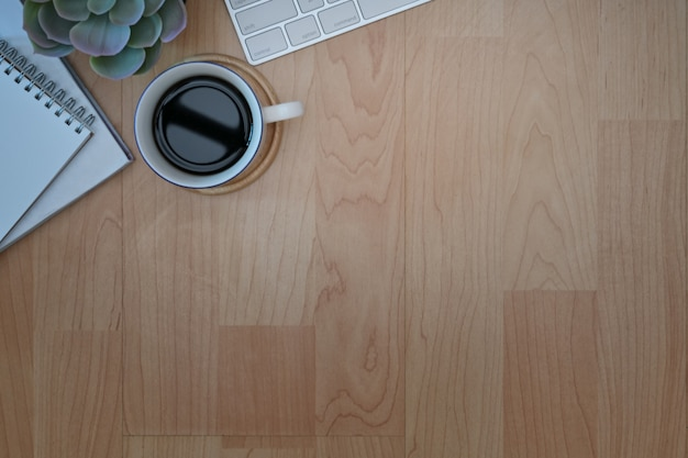 Top view of workplace with coffee mug,  keyboard, office supplies on wooden table