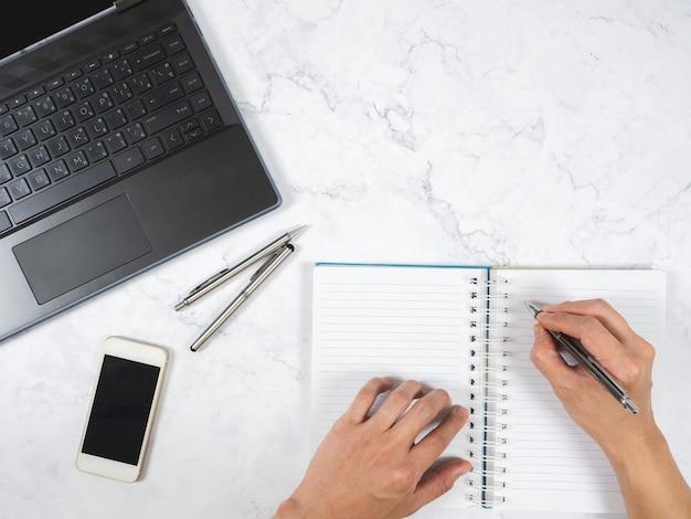 상단 보기 작업 공간 대리석 테이블 손으로 노트북에 펜, 휴대폰, 노트북 공간 쓰기
