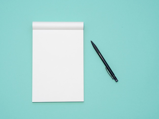 Top view workspace mockup on aqua background with open notebook and pen