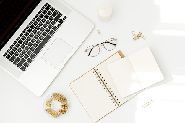 Top view workspace mockup on white with notebook, accessories, candle and glasses