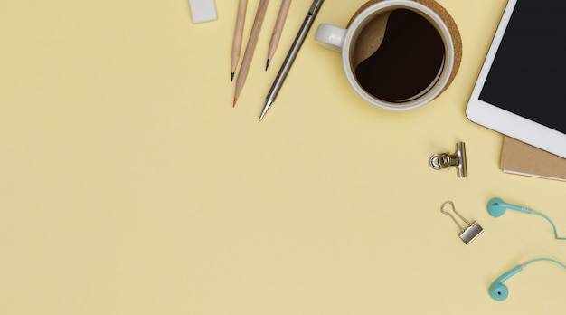 Top view workspace office supplies mockup with tablet, hot coffee cup, books and accessories isolated on yellow background, overhead view with copy space, workspace for designer concept
