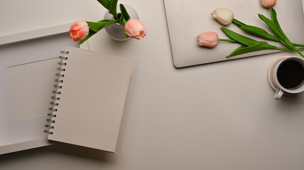 Top view of workspace with blank notebook, frame, copy space and flower decorated on the table