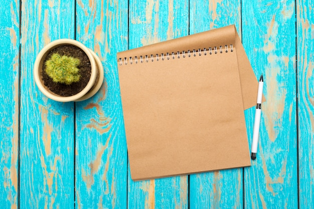 Top view workspace with blank notebook and pen on wooden table background
