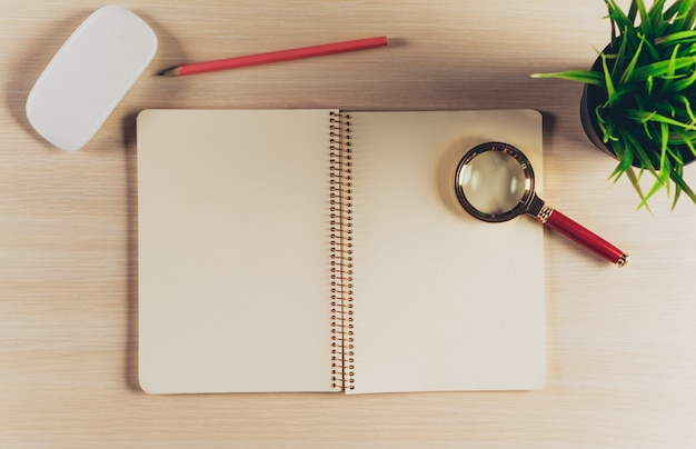 Top view workspace with blank notebook and pen on wooden table