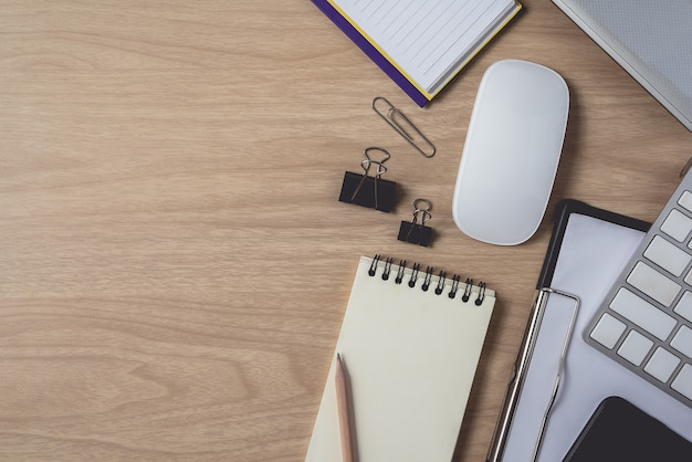 Top view of workspace with diary or notebook and clipboard, laptop, mouse computer, keyboard, smart phone, pencil, pen on wooden background