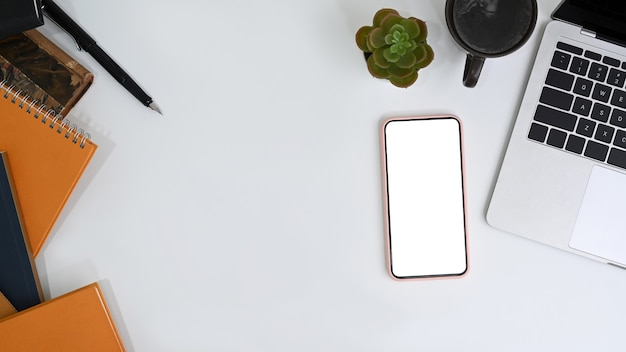 Top view workspace with empty screen of mobile phone and office supplies on white office desk.