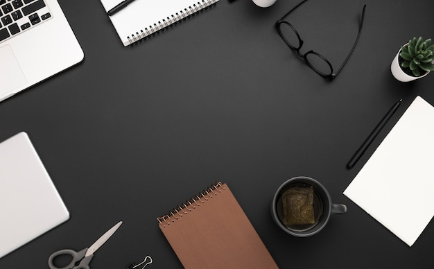 Top view of workspace with glasses and cup of tea