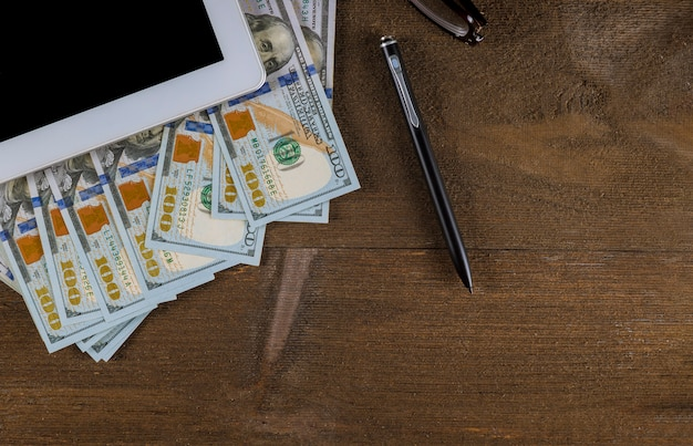 Top view workspace with money dollar bills and pen on wooden table background