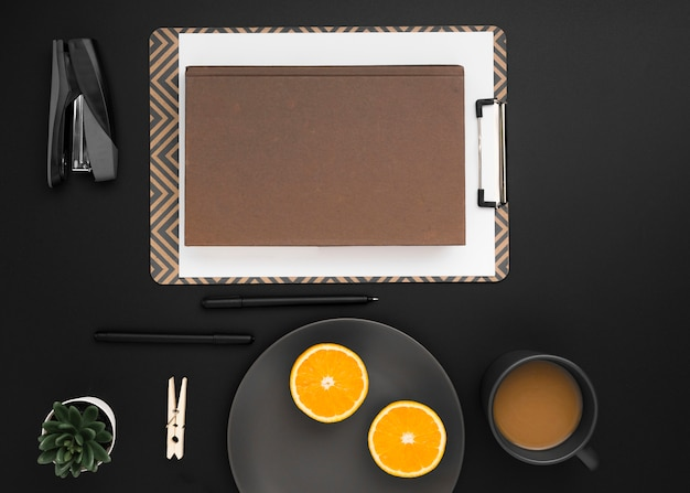 Top view of workspace with notepad and plate of orange slices