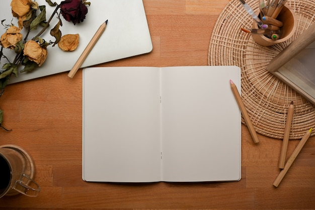 Top view of workspace with opened blank notebook and flowers on wooden table