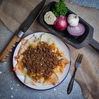 Вид сверху ксенгеля с йогуртом и луком и чесноком и вилкой и ножом в круглой тарелке