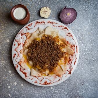 Вид сверху ксенгеля с йогуртом и луком и чесноком в круглой тарелке