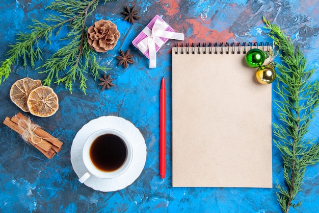 Top view xmas balls on a notebook pine tree branches cinnamon sticks anises dried lemon slices a cup of tea on blue surface