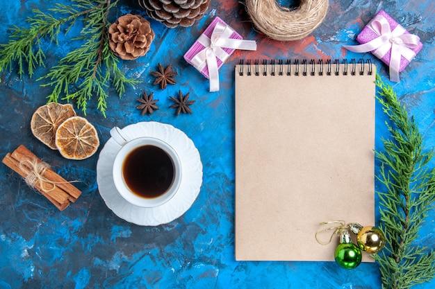 Вид сверху рождественские шары на ноутбуке ветки сосны палочки корицы анис сушеные дольки лимона чашка чая на синей поверхности