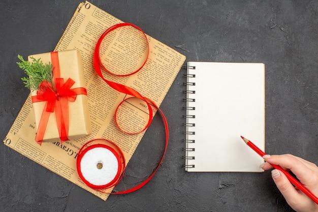 Regalo di natale di vista superiore in nastro di abete del ramo di carta marrone sulla matita del blocco note del giornale in mano femminile su superficie scura