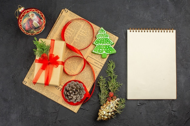 Top view xmas gift in brown paper branch fir ribbon on newspaper xmas ornaments a notebook on dark surface