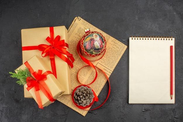 Vista dall'alto regalo di natale in nastro di carta marrone albero di natale giocattolo su giornale una matita un quaderno su superficie scura dark