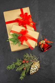 Top view xmas gift in brown paper tied with red ribbon branch fir xmas tree ornaments on dark background