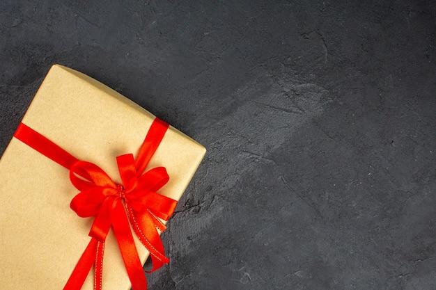 Regalo di natale vista dall'alto in carta marrone legato con nastro rosso su superficie scura