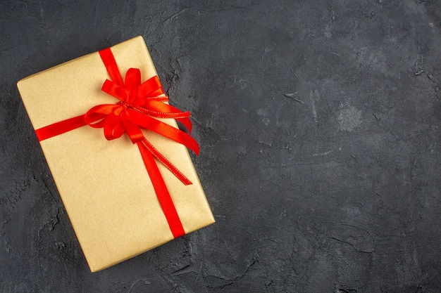 Regalo di natale vista dall'alto in carta marrone legato con nastro rosso su superficie scura Foto Gratuite