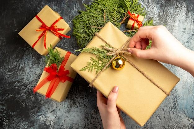 Vista dall'alto regalo di natale in mano femminile piccoli regali rami di pino su superficie grigia