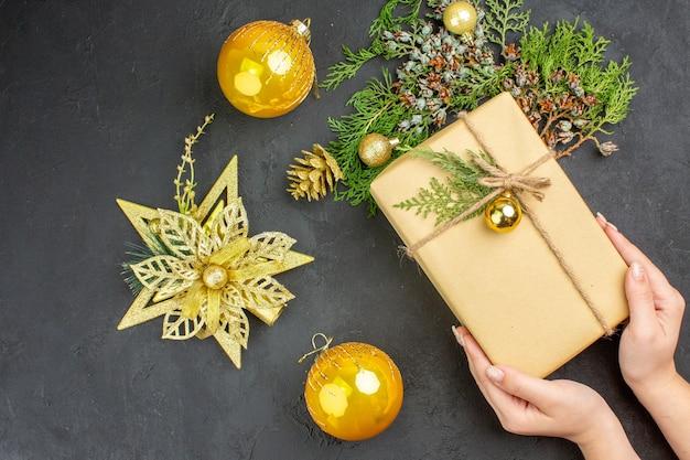 상위 뷰 크리스마스 선물 전나무 나뭇가지 베이지색 표면에 크리스마스 트리 장난감