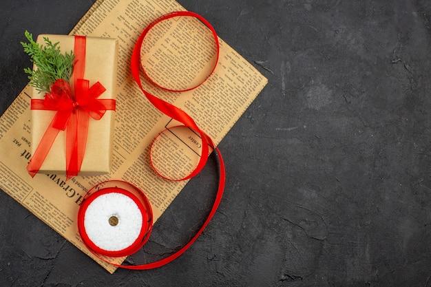 어두운 표면에 신문에 갈색 종이 분기 전나무 리본에 상위 뷰 크리스마스 선물