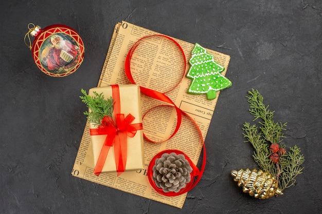 어두운 표면에 신문 크리스마스 장식품에 갈색 종이 분기 전나무 리본에 상위 뷰 크리스마스 선물