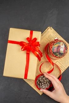 어두운 표면에 여성 손에 신문에 갈색 종이 리본 크리스마스 트리 장난감의 상위 뷰 크리스마스 선물