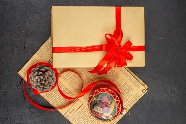 어두운 표면에 신문에 갈색 종이 리본 크리스마스 트리 장난감의 상위 뷰 크리스마스 선물
