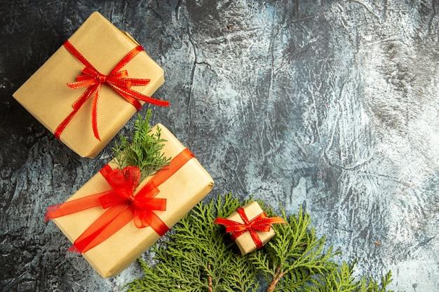 Vista dall'alto regalo di natale piccoli regali rami di pino su sfondo grigio spazio copia