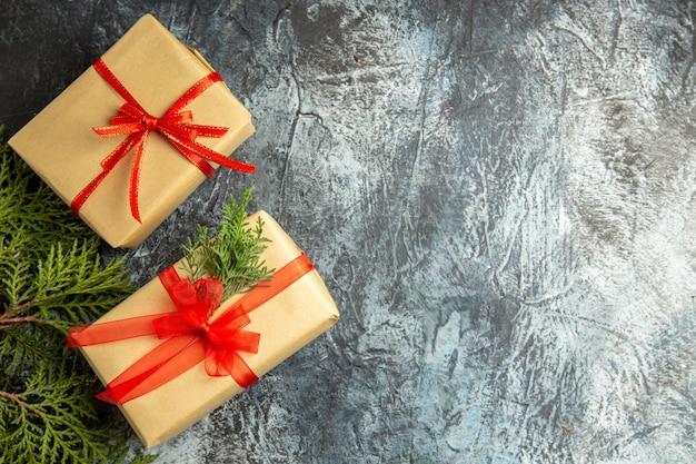 Vista dall'alto regalo di natale piccoli regali rami di pino su superficie grigia