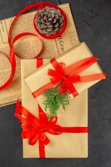 Vista dall'alto regali di natale in nastro di abete ramo di carta marrone su pigna di giornale su superficie scura