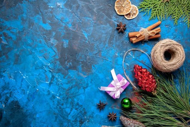 Vista dall'alto regali di natale abete rami coni anice su sfondo blu posto libero