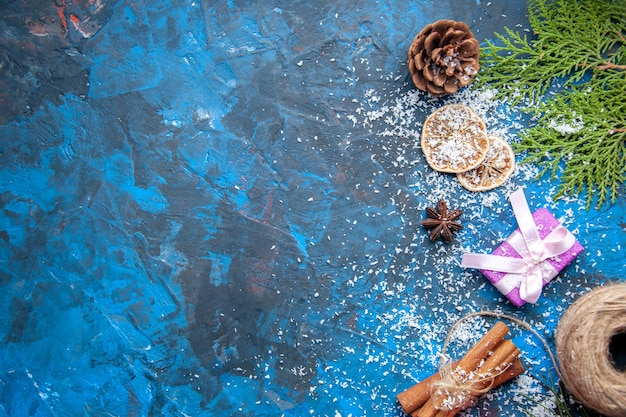 Top view xmas gifts fir tree branches cones anises on blue background