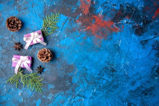Vista dall'alto regali di natale abete rami coni anice su sfondo blu