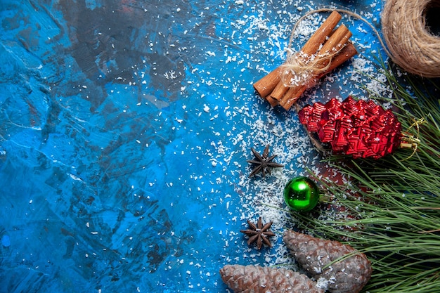 Top view xmas gifts fir tree branches cones anises on blue surface