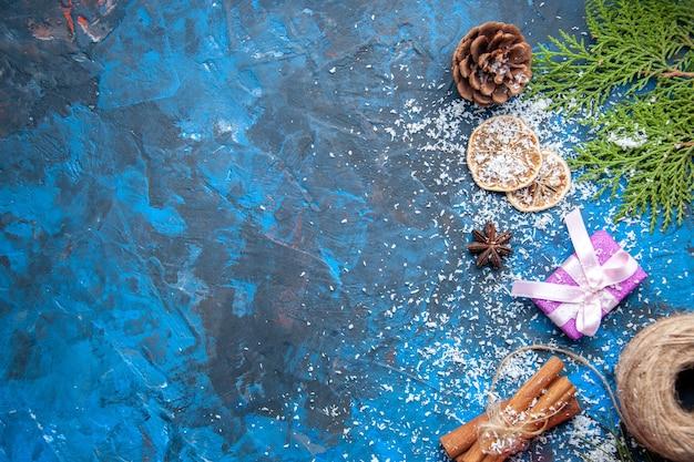 Vista dall'alto regali di natale abete rami coni anice su superficie blu