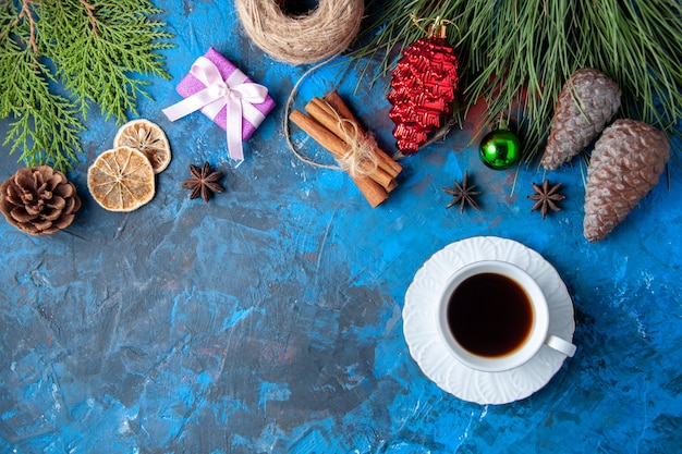 Top view xmas gifts fir tree branches cones anises a cup of tea on blue surface
