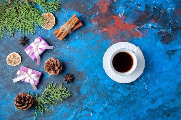 Vista dall'alto regali di natale abete rami coni anice tazza di tè su superficie blu