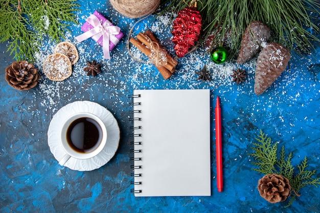 Vista dall'alto regali di natale abete rami coni anice quaderno una tazza di tè su superficie blu