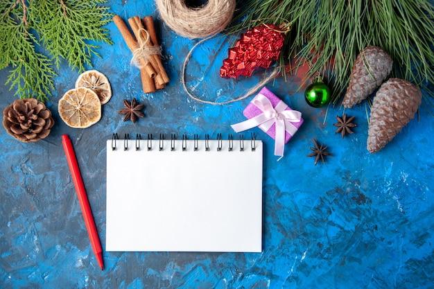 Vista dall'alto regali di natale abete rami coni anice quaderno matita rossa su superficie blu