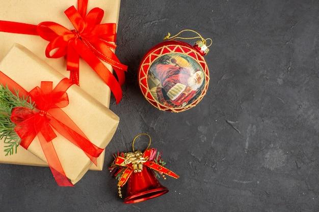 어두운 표면에 빨간 리본 크리스마스 트리 장난감으로 묶인 갈색 종이의 상위 뷰 크리스마스 선물