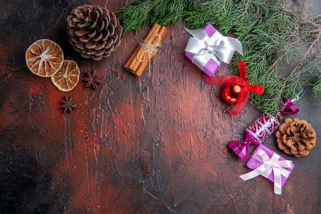 상위 뷰 크리스마스 선물 소나무 나무 가지에 콘 크리스마스 트리 장난감 계피 말린 레몬 조각 아니스를 진한 빨간색 표면에
