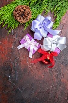 Vista dall'alto regali di natale ramo di albero con cono albero di natale giocattolo su superficie rosso scuro dark