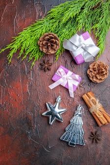 Вид сверху рождественские подарки с розовой коробкой и белой лентой, ветка аниса, корица, елочные игрушки на темно-красной поверхности