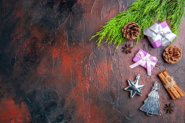 분홍색 상자와 흰색 리본 나무 가지가 있는 상위 뷰 크리스마스 선물은 진한 빨간색 표면에 계피 크리스마스 트리 장난감을 제공합니다.