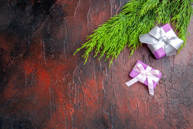 Top view xmas gifts with pink box and white ribbon tree branch on dark red background